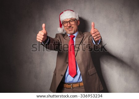 conident santa claus business man making the ok thumbs up hand sign in studio - stock photo