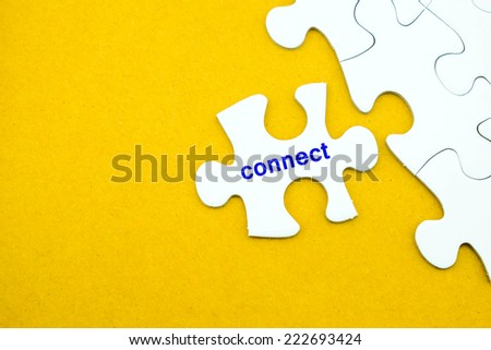 Connect word on white jigsaw in hand on yellow background, social media concept - stock photo