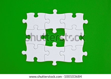 Connected blank puzzle pieces isolated on a green background. - stock photo