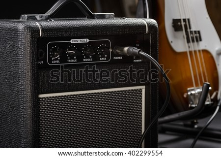 Connected cable in guitar amp from the electric bass near it. Four strings on musical instrument. Differently colored guitar. - stock photo