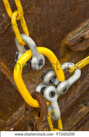 Connected Old Rusting Chains with rusting steel in background - stock photo