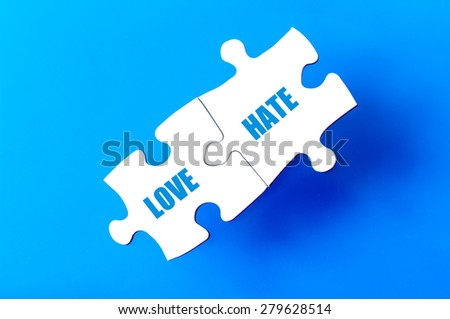 Connected puzzle pieces with words LOVE and HATE  isolated over blue background, with copy space available. Business concept image. - stock photo
