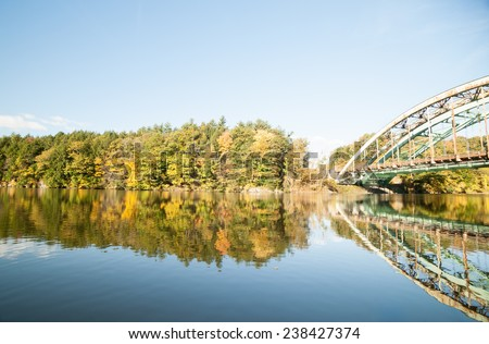 Connecticut River, morning calm and fall colors with US Navy Seabees Bridge. - stock photo