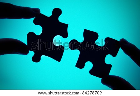 connecting two pieces of puzzle - stock photo