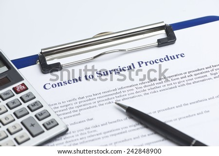 Consent for surgical procedure with calculator on white table. - stock photo