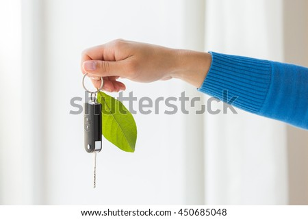 conservation, environment, people, transport and ecology concept - close up of hand holding car key with green leaf trinket - stock photo
