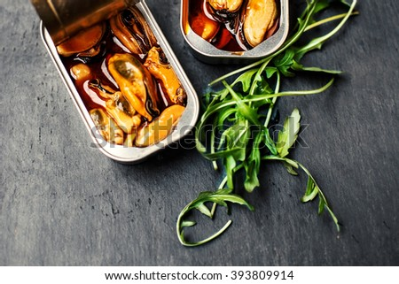 Conserved mussels in a can over black background close up / Delicious food  - stock photo