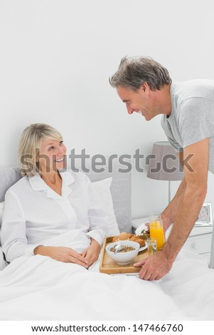 Considerate man bringing breakfast in bed to his partner at home in bedroom