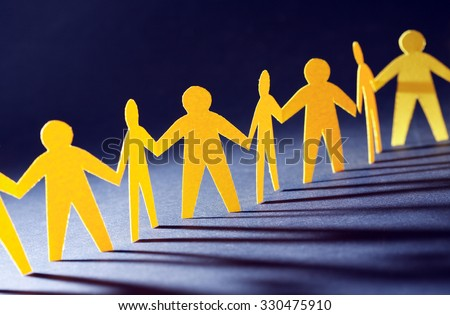 Consolidation concept. Yellow paper men in a row on dark background - stock photo