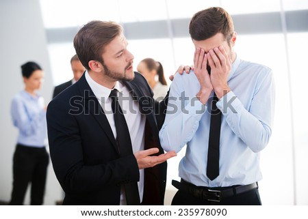 Consoling his hopeless colleague. Young businessman consoling his depressed colleague with people standing in the background  - stock photo
