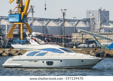 CONSTANTA, ROMANIA - MAY 27, 2014: Modern luxurious white speedboat yacht floats in the shipyard bay of commercial port of Constanta, the largest port on the Black Sea and the 18th largest in Europe. - stock photo