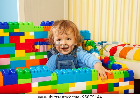 Constructing with toy blocks is fun - kid playing with toy plastic blocks - stock photo