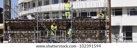 construction and scaffolding workers, panoramic view - stock photo