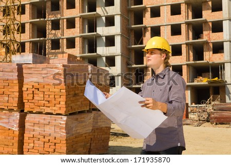 Construction architects review plans at a construction site with crane. - stock photo