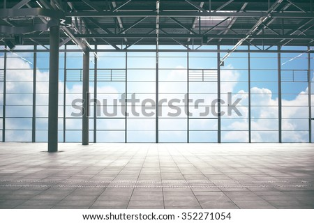 construction, architecture and building concept - airport terminal empty room over blue sky and clouds background - stock photo