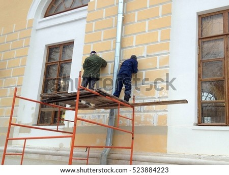 Construction builder workers process walls without any safety equipment in winter