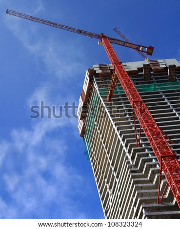 Construction building with crane background with blue sky - stock photo
