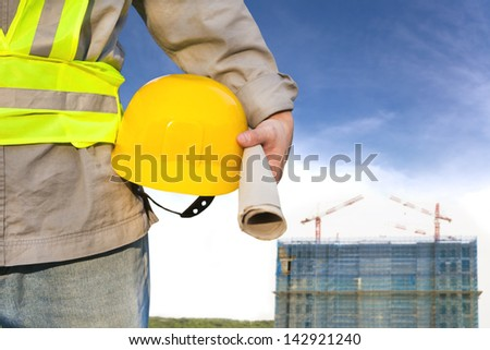 Construction building with worker holding hat - stock photo