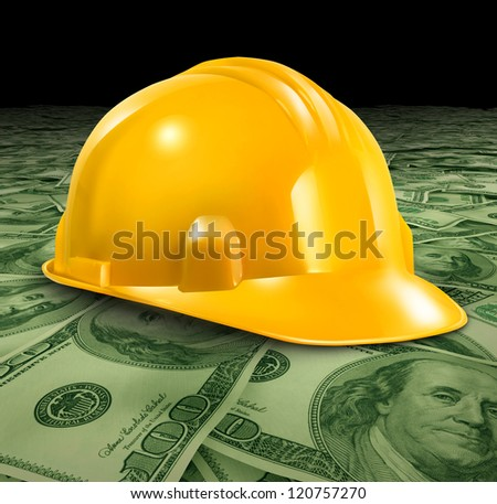 Construction business with a yellow hardhat helmet on a floor of money and currency representing the economic condition of commercial and residential building activity and investment. - stock photo