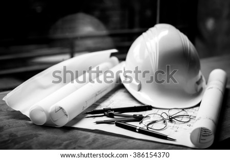 construction concept image helmet rolled blueprints on wooden boards. - stock photo