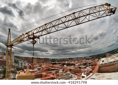 Construction crane against the grey sky and city houses - stock photo