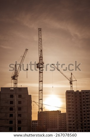 Construction crane and skyscraper at sunset.