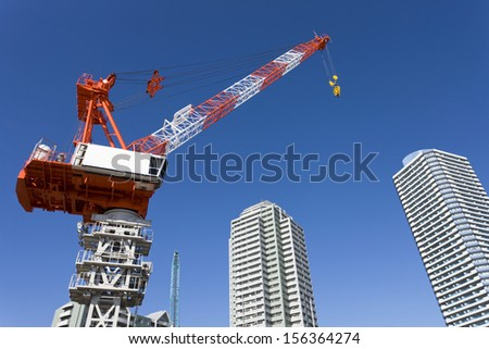 Construction crane in front of new modern apartment building - stock photo