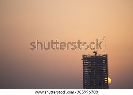 construction cranes and building silhouettes over sun at sunrise - stock photo