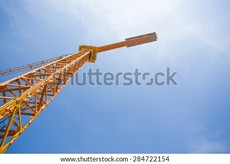 construction cranes and the blue sky with clouds. Taken from the bottom up - stock photo