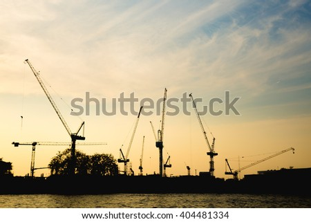 Construction cranes in evening Construction cranes are building in the evening. - stock photo