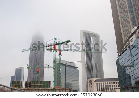 Construction cranes in the middle of the city of Frankfurt surrounded by fog