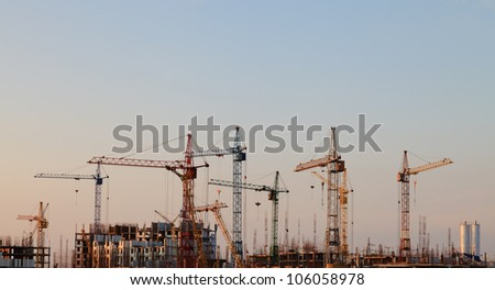 Construction cranes in the sky at sunset - stock photo