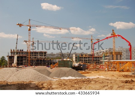 Construction cranes on a blue sky background - stock photo
