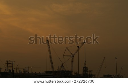 Construction cranes stopped for the evening. - stock photo