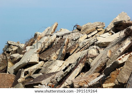 Construction debris - reinforced concrete blocks rusty armature against blue sky background - stock photo