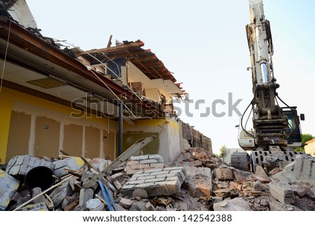 Construction/demolition site with debris pile in foreground, excavator and partly destroyed building in background. - stock photo