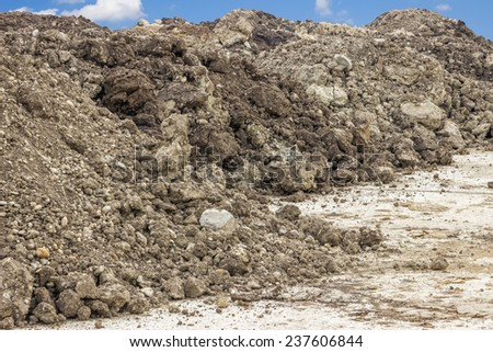 Construction dirt pile under blue sky and clouds - stock photo