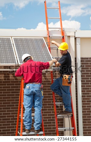 Construction electricians installing solar panels on the side of a building. - stock photo