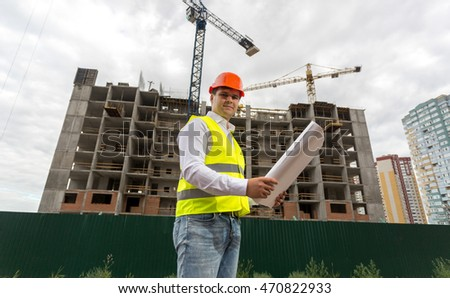 Construction engineer in hardhat on building site at cloudy day