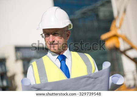 Construction engineer in hardhat with project in hands - stock photo