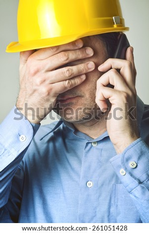 Construction Engineer just Heard Bad News From his Employees over Mobile Phone. - stock photo