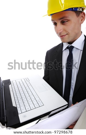 Construction engineer using his laptop computer and blueprints in the job - stock photo