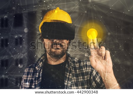 Construction engineer with VR goggles managing building project - stock photo