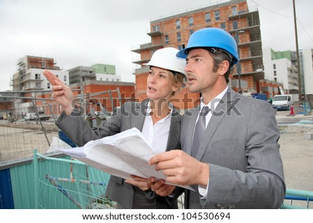 Construction engineers checking plan on building site - stock photo