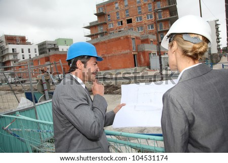 Construction engineers checking plans on building site - stock photo