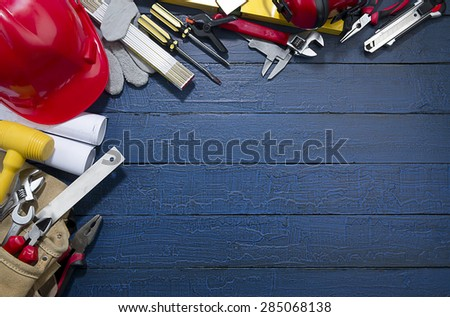 Construction equipments on blue wood background with copy space. - stock photo