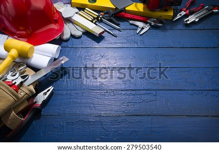 Construction equipments on blue wood background with spot lightened space for your text. Blueprints are not subject to copyright. Words on them are regular like kitchen, bedroom, bathroom etc.   - stock photo