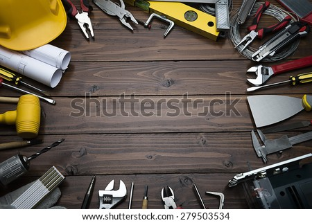 Construction equipments on brown wood background with copy space.  Blueprints are not subject to copyright. Words on them are regular like kitchen, bedroom, bathroom etc. - stock photo