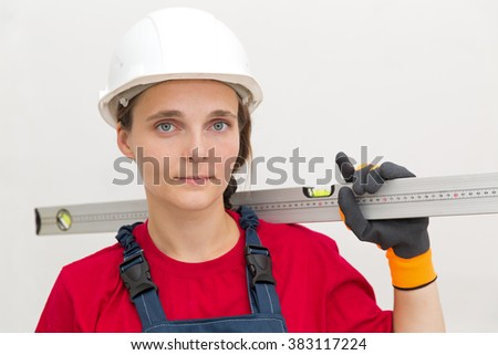 Construction female worker with level tool on house wall background - stock photo