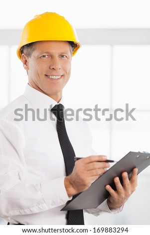Construction foreman. Cheerful mature man in formalwear and hardhat writing something in his note pad and smiling at camera - stock photo